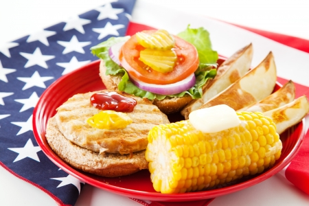 Healthy turkey burger on whole grain bun, with baked potato wedges and corn on the cob  Low fat picnic on an American Flag  Horizontal View photo