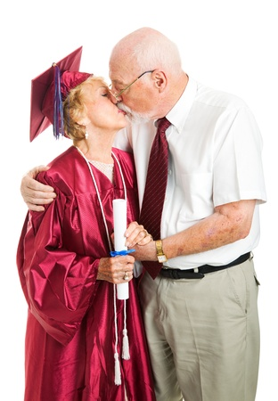 Senior woman gets a kiss from her husband on her graduation day   Isolated on white  photo