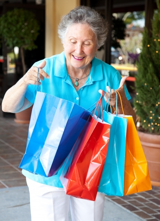 Senior woman smiles as she looks into her shopping bags to check out what she Stock fotó