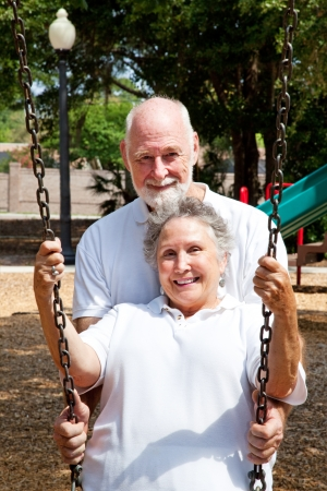 columpios: Marido romántico senior de empujar su encantadora esposa en un columpio en un parque