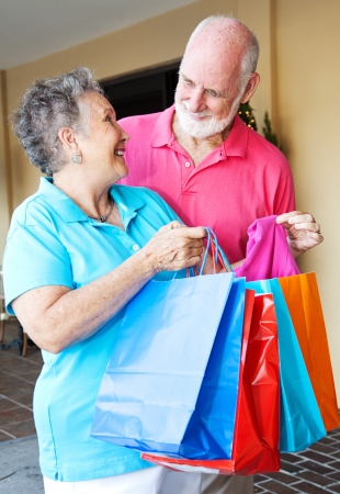 Senior woman shows her husband some of the bargains she got shopping    Stock Photo - 14431150
