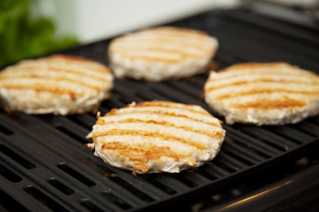 nonstick: Healthy low fat turkey burgers cooking on the grill   Stock Photo