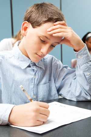 school exam: Boy taking test in class.  Real person in real-life classroom situation.   Stock Photo