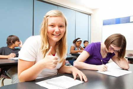 gives: Pretty blond teen gives a thumbs up because she did well on a school test.