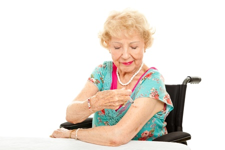 Senior woman in a wheelchair, giving herself an injection.  White background. Stock Photo - 14431200