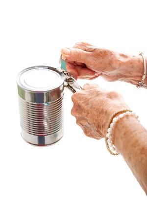 hand crank: Primer plano de las manos de los ancianos, con la artritis, que luchan por utilizar un abrelatas. Aislado en blanco.