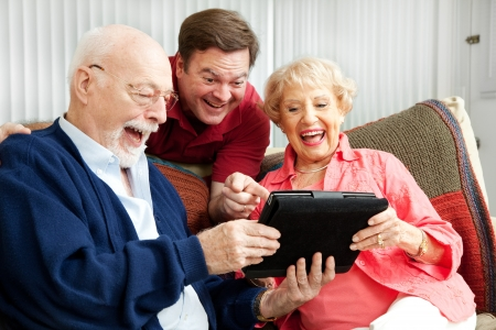 Laughing family, senior parents and their adult son, using a tablet PC.