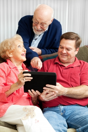 Senior couple learns how to use their new tablet PC from their adult son.   photo