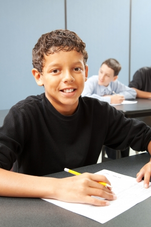 writing black: Handsome ethnic boy in school class.  Real person in real classroom.