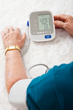 Closeup of a senior man's arm hooked up to a home blood pressure machine, showing his results.   photo