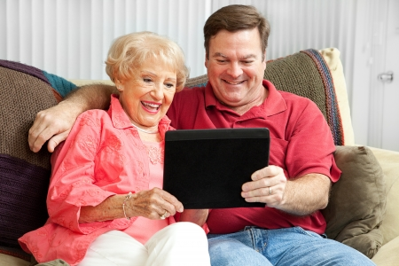 Son teaching his elderly mother to use a new tablet PC. Stock Photo - 14431260