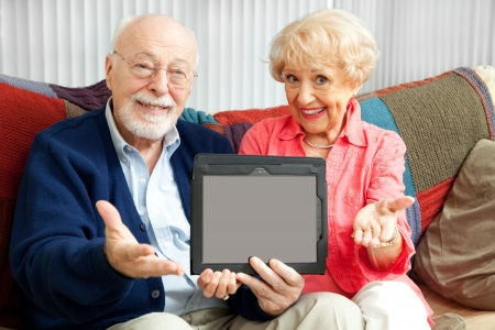 family sofa: Senior couple holding up a blank tablet PC, ready for your text or picture.