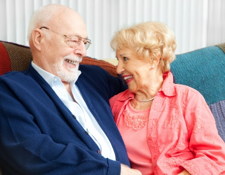 Senior couple in love, flirting on the couch.   photo