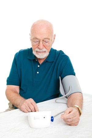 hipertension: Senior hombre utilizando una m�quina de presi�n arterial en el hogar para comprobar sus estad�sticas vitales. Blanco fondo. Foto de archivo