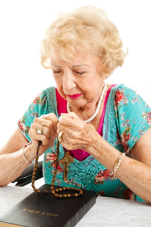 Catholic, Christian elderly woman with her bible, praying the rosary.  White background. photo