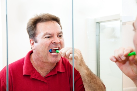 Man in his forties brushes his teeth looking in the bathroom mirror.   photo