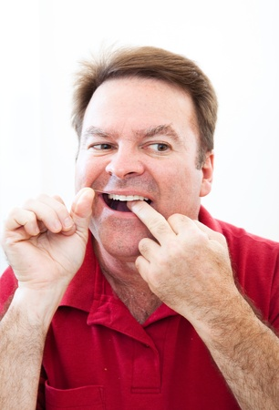 flossing: Man flossing his teeth in the mirror.  Good oral hygiene.   Stock Photo