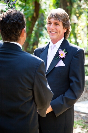 Newly married gay couple posing for a portrait under the wedding arch    photo