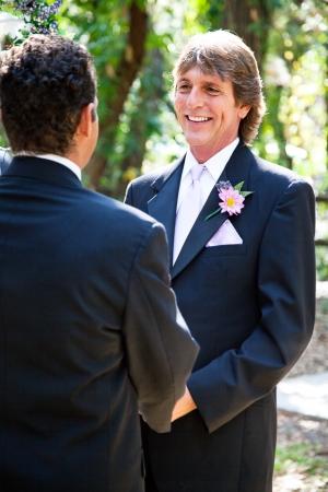 boda gay: Pareja de recién casados ??gay posando para un retrato bajo el arco de la boda Foto de archivo