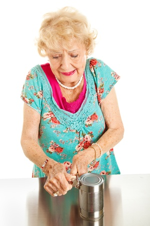 Senior woman with arthritis struggles to open a can    photo
