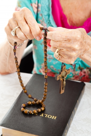 Senior woman praying the rosary with her beads and her bible   Shallow depth of field with focus on her fingers holding the beads  photo