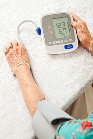 Senior woman using an automatic blood pressure cuff  to monitor her health at home    photo
