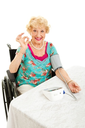 own blood: Disabled senior woman in wheelchair taking her own blood pressure at home and giving the okay sign   White background