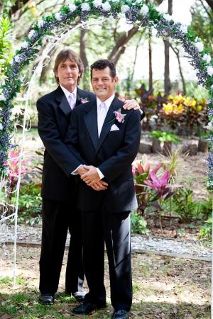 boda gay: Pareja de recién casados ??gay posando para un retrato bajo el arco de la boda.