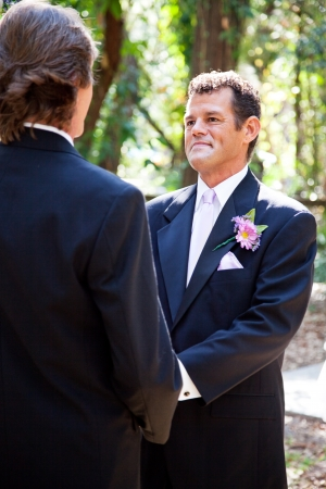 Handsome hispanic groom marrying his same sex partner in an outdoor wedding ceremony.   photo