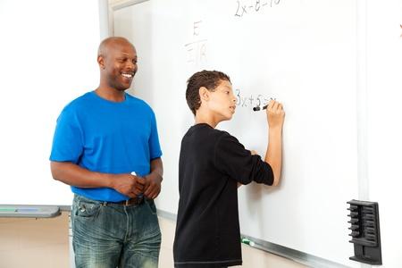 high school teacher: African American math teacher helping a student to pre-algebra on the board.