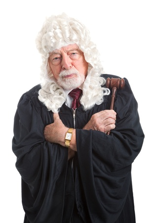 British judge in a wig, with his arms crossed looking stern, serious, and angry.  Isolated on white.   Stock Photo