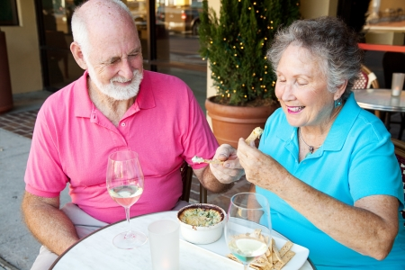 Senior couple on a date enjoys an artichoke dip appetizer.   photo