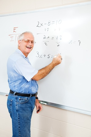 Middle aged teacher or adult education student writing algebra equations on the board.   photo