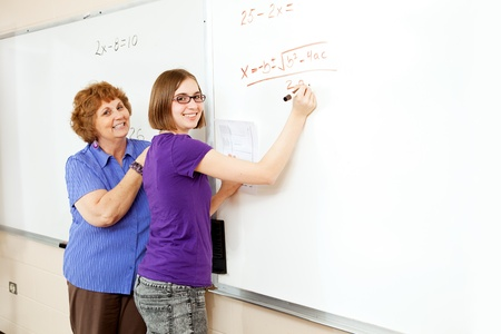 Math student and teacher working problems on the white board, with blank whiteboard space for text.   photo
