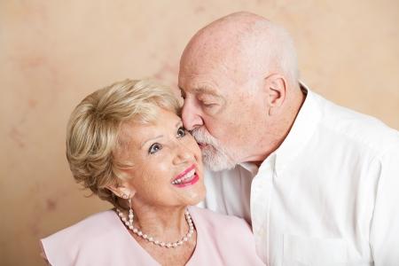 cheek: Senior man gives his beautiful wife a kiss on the cheek.   Stock Photo