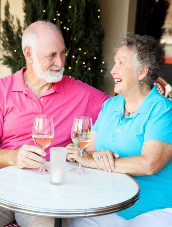 Senior couple enjoying a glass of wine and conversation at an outdoor cafe.   photo
