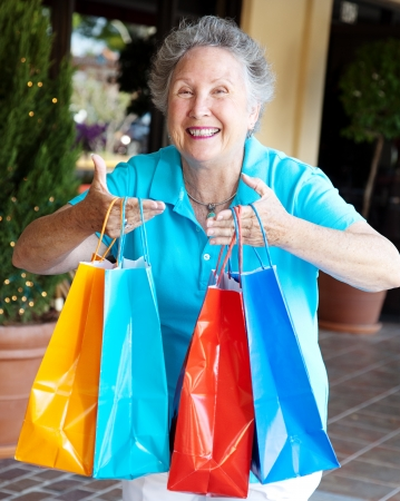 Senior woman addicted to shopping, holding up a handful of bags.   photo