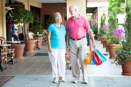 Senior couple shopping together at an outdoor mall, holding hands.   photo