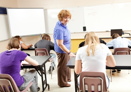 Math teacher gives a test in pre-algebra to her high school students.   photo