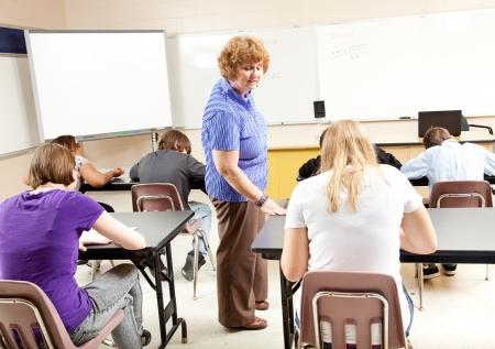 estudiantes de secundaria: Profesor de matem�ticas le da una prueba de pre-�lgebra a sus estudiantes de secundaria. Foto de archivo