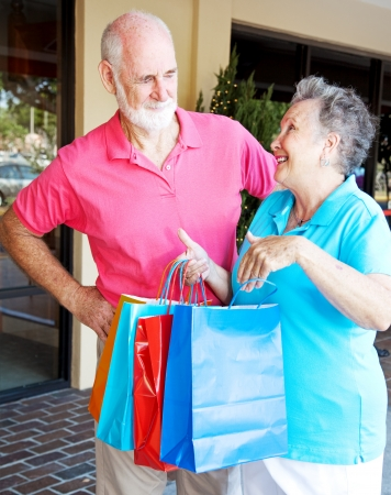 Husband looks disgusted with his wife who has spent too much money shopping.   photo