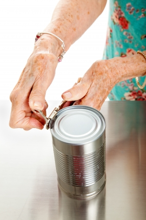 Senior woman's hands with arthritis, struggling to open a can.   photo