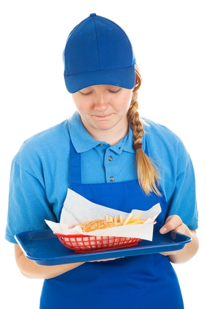 Teenage fast food worker disgusted by the burger and fries shes serving.  Isolated on white. photo