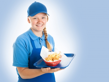 Teenage fast food worker holding a tray of chicken nuggets and fries. Blue background photo