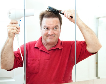 Mature man blow drying his hair in the bathroom mirror.   photo
