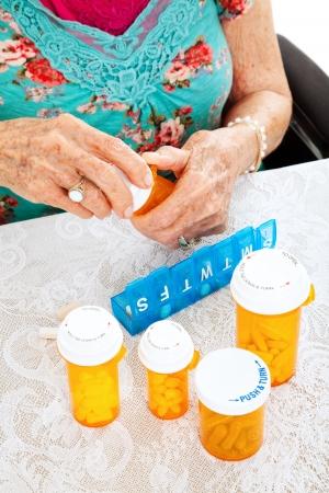 sorting: Senior woman sorting her pills for the week.