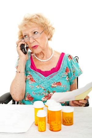 medical bill: Senior woman on the phone discussing her medical bills with the health insurance company.  White background.