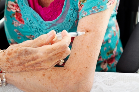 injection woman: Closeup of a senior womans hands as she gives herself a shot in the arm.