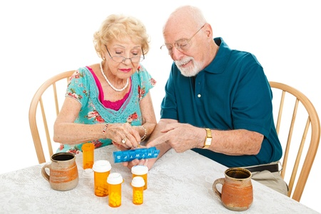 Senior couple at the table, sorting their medications for the week.  White background.