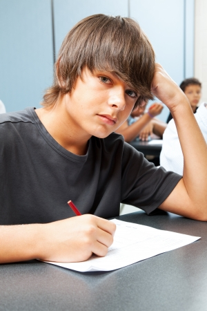 Serious adolescent school boy taking a test in class.   photo